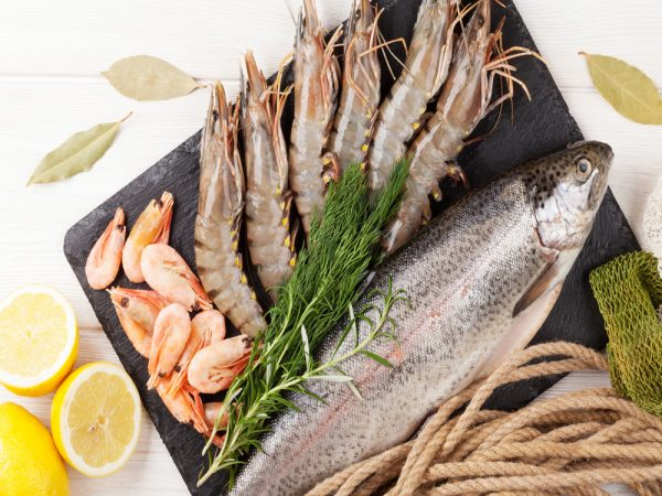 Fresh raw sea food with spices on wooden table background. Top view